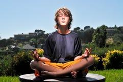 Junge in einer Yogahaltung draußen auf einer Tabelle Stockbilder