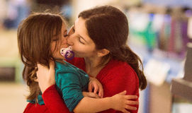 Junge eines jungen Mädchens, das ihre Schwester küsst Stockfoto