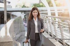 Junge elegante Asien-Geschäftsfrau mit Handgepäck und tablet a Lizenzfreie Stockfotografie