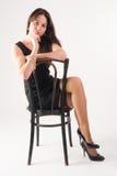 Junge elegante Frau auf Stuhl Lizenzfreie Stockbilder