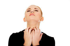 Junge elegante Frau, die ihren Hals verkratzt lizenzfreie stockfotografie