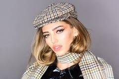 Junge elegante Frau im modischen Hut und im Schal Blondes Haar auf grauem Hintergrund Lizenzfreie Stockfotos
