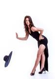 Junge elegante Frau im schwarzen Kleid, das ihren Hut lässt, fallen unten Stockbild