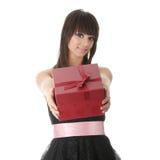 Junge elegante Frau im schwarzen Kleid mit Geschenk Stockfotografie