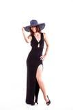 Junge elegante Frau im schwarzen Kleid mit Hut an Stockbild