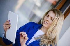 Junge elegante Geschäftsfrau im Matrosen, der Tablette hält stockfotografie