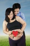 Junge Eltern, die Herzsymbol halten Stockbild