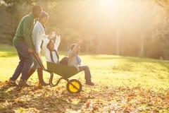 Junge Eltern, die ihre Kinder in einer Schubkarre halten Stockfoto