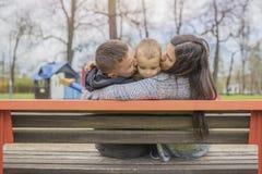 Junge Eltern, die mit ihrem Kind im Park, in der Natur genießen lizenzfreie stockfotografie