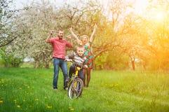 Junge Eltern, die seinen Sohn unterrichten, ein Fahrrad zu reiten Lizenzfreie Stockfotografie