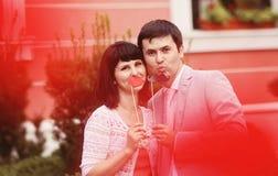 Junge Eltern, die Spaß mit dem Schnurrbart und Lippen hergestellt vom Papier haben Lizenzfreies Stockfoto