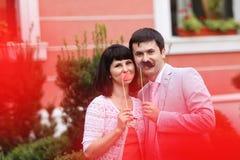 Junge Eltern, die Spaß mit dem Schnurrbart und Lippen hergestellt vom Papier haben Lizenzfreie Stockbilder