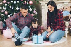 Junge Eltern Familienvater und Frau mit Kinderöffnendem Weihnachten stockbilder