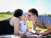 Junge Eltern mit dem Baby im Freien im Park Lizenzfreies Stockfoto