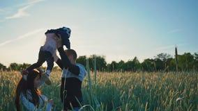 Junge Eltern mit einer kleinen Tochter auf dem Feld unter den grünen Ährchen des Weizens genießen den Sonnenuntergang Nehmen sie stock video footage