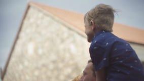 Junge Eltern mit ihrem entzückenden Sohn, der Spaß im Hof küsst und hat stock footage