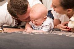 Junge Eltern trösten ihr schreiendes Baby stockfotos
