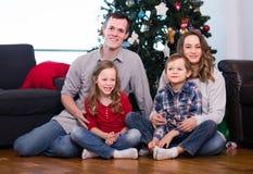 Junge Eltern und Kinder, die für Foto durch Weihnachtsbaum aufwerfen Lizenzfreies Stockbild