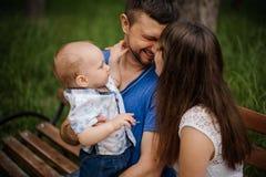 Junge Eltern und kleiner Sohn in der glücklichen Familie des Parks, die auf Bank sitzt stockbild