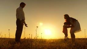 Junge Eltern unterrichten Kind, mit ihren Füßen in den Strahlen des goldenen Sonnenuntergangs zu gehen stock video footage