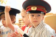 Junge in emporgeragter Kappe im Kostüm des Polizisten Stockbild