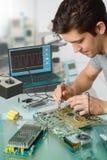 Junge energische männliche Technologie oder Ingenieur repariert elektronisches equipme Lizenzfreie Stockbilder
