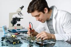Junge energische männliche Technologie oder Ingenieur repariert elektronisches equipme Lizenzfreies Stockfoto