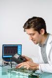 Junge energische männliche Technologie oder Ingenieur repariert elektronisches equipme Stockfoto