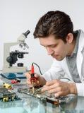 Junge energische männliche Technologie oder Ingenieur repariert elektronisches equipme Stockbilder