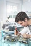 Junge energische männliche Technologie oder Ingenieur repariert elektronisches equipme Stockfotografie