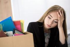 Junge entließen Arbeitnehmerin im Büro, das nahe Kartonkasten sitzt Stockbilder