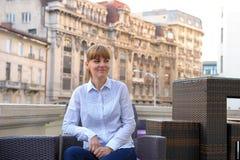 Junge entschlossene Geschäftsfrau, die bei Tisch auf Büro builin sitzt Lizenzfreies Stockfoto
