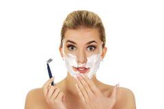 Junge entsetzten die Frau, die ihr Gesicht mit einem Rasiermesser rasiert stockfotografie