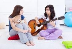 Junge entspannende und sprechende Mädchen Lizenzfreies Stockfoto