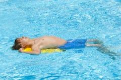 Junge entspannt sich auf seinem Boogiebrett im Pool Stockbild