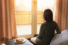 Junge entspannte Frau, die das Fenster betrachtet Stockfotografie