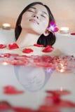 Junge entspannte Frau, die am Gesundheits-Badekurort badet Stockbild