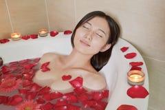 Junge entspannte Frau, die am Gesundheits-Badekurort badet Stockbilder