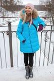 Junge entzückende blonde Frau der Ganzaufnahme, die den blauen mit Kapuze Mantel schlendert in Stadt-Parkbrücke des verschneiten  Stockbilder
