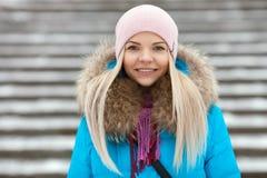 Junge entzückende blonde Frau, die den blauen mit Kapuze Mantel schlendert in Stadt-Parkbrücke des verschneiten Winters trägt Jah Stockbild