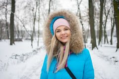 Junge entzückende blonde Frau, die den blauen mit Kapuze Mantel schlendert in Stadtpark des verschneiten Winters trägt Jahreszeit Stockfoto