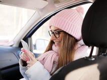 Junge entzückende Blondine im rosa Strickmützeschal, der in der Hand im Auto mit Winter des Telefons draußen sitzt Stockbilder