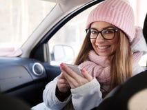 Junge entzückende Blondine im rosa Strickmützeschal, der in der Hand im Auto mit Winter des Telefons draußen sitzt Lizenzfreies Stockfoto