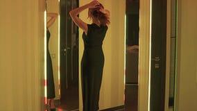 Junge entzückende Frau in schwarzem coctail Kleid, das nahe dem Spiegel mit Neonröhren überschreitet Halt für eine Weile, zum sie stock video