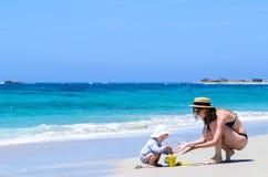Junge entzückende Mutter, die Spaß mit kleiner Tochter am tropischen Strand hat lizenzfreies stockbild
