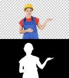 Junge Erbauerarbeitskraftfrau, die Produkt mit ihren Händen von ihren Seiten, Alpha Channel zeigend sich darstellt stockbilder