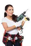 Junge Erbauerfrau mit einem Bohrgerät Lizenzfreie Stockfotografie