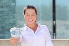 Junge erfolgreiche Frau, die Eurobanknoten in der Straße gibt Stockfoto