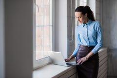 Junge erfolgreiche glückliche lächelnde Geschäftsfrau auf Laptop Stockfoto