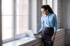 Junge erfolgreiche glückliche lächelnde Geschäftsfrau auf Laptop Lizenzfreie Stockfotos